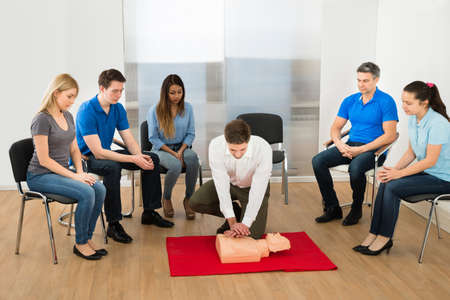 First Aid Instructor Showing Resuscitation Technique On Dummy photo