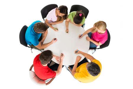 Vysoký úhel pohledu lidí, kteří sedí na židli psaní na stole