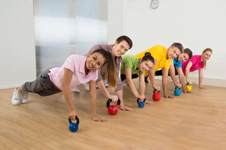Happy Diverse Multiethnic Group Of Friends Exercising Together With Kettle Bell photo