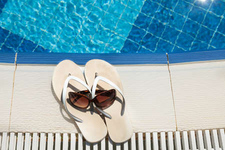 swimming pool: High angle view of flip flops and sunglasses beside swimming pool