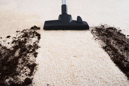 dirty room: Photo Of Vacuum Cleaner Cleaning Dirt On Carpet Stock Photo