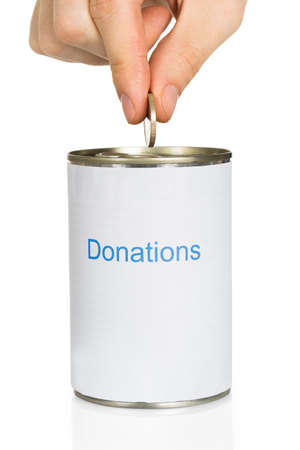 Persons Hand Putting Coin In Donation Can Over White Background
