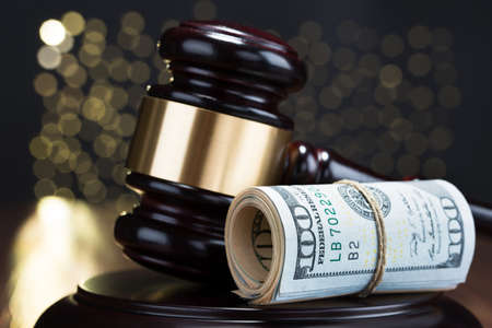 lawsuit: Close-up Of Wooden Gavel With Rolled Banknote Tied With Rope Stock Photo