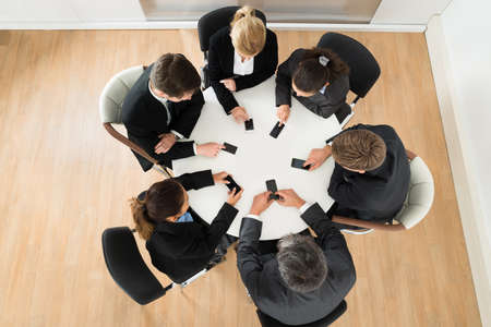 Group Of Businesspeople Using Cell Phone Sitting At Table photo