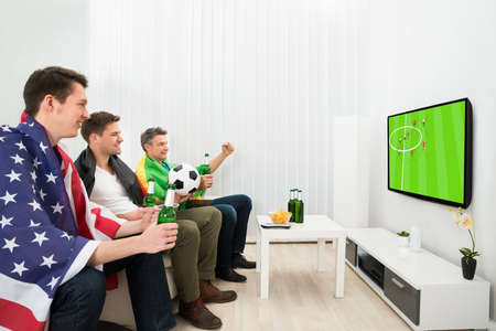 watching football: Group Of Friends From Different Nations Holding Beer Bottle Watching Football On Television Stock Photo