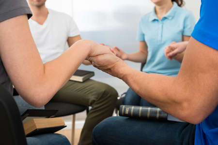 hombre orando: Primer plano de personas que sostienen cada otros manos orando juntos
