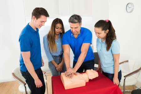 teknik: Hälsa klass Instruktör påvisar Cpr Livräddnings Tekniker till studenter Stockfoto