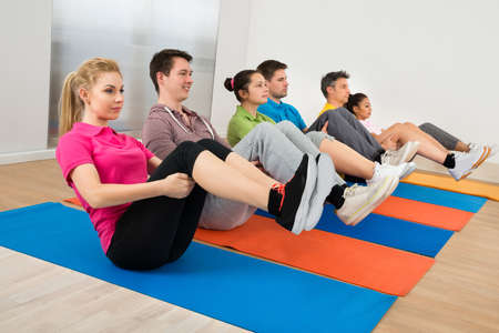 Multiethnic Group Of People Exercising On Mat At Gym photo