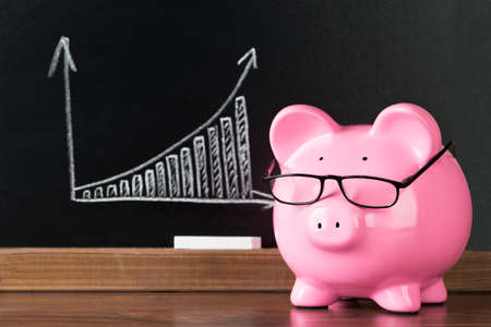 Pink Piggybank With Glasses On Desk In Front Of Blackboard Showing Graph