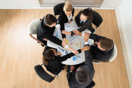 joining hands: High Angle View Businesspeople Team Joining Hands In Office Stock Photo