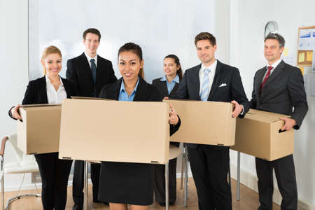 moving box: Portrait Of Happy Multiethnic Employees In Office Holding Cardboard Boxes