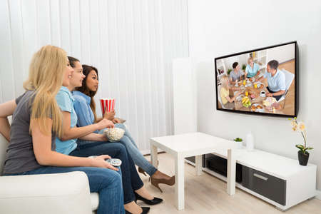 sofa television: Happy Multiethnic Young Women Sitting On Couch Watching Movie