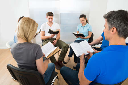 bibles: Group Of Multiethnic Friends Reading Bible Together Stock Photo