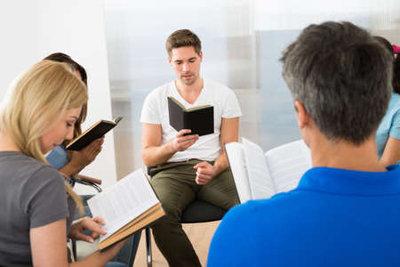 holding bible: Group Of Multiethnic Friends Reading Bible Together Stock Photo
