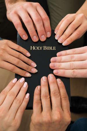 familia orando: Grupo de personas mantiene la Biblia y orando juntos Foto de archivo