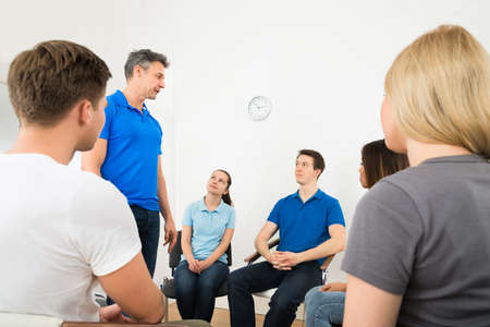 terapia grupal: Grupo de personas Mirando a hombre Explicando