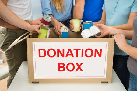 donate: Group Of People Putting Cans In Donation Box