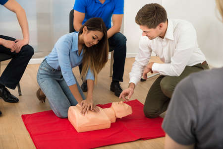 Instructor Demonstrating Cpr Chest Compression On A Dummy photo