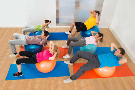 pilates man: High Angle View Of People Exercising On Pilate Ball Stock Photo