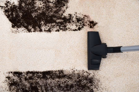 carpet and flooring: Photo Of Vacuum Cleaner Cleaning Dirt On Carpet Stock Photo
