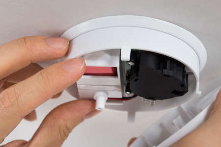 incendio casa: Close-up foto de Handyman Reparación del detector de humos Foto de archivo