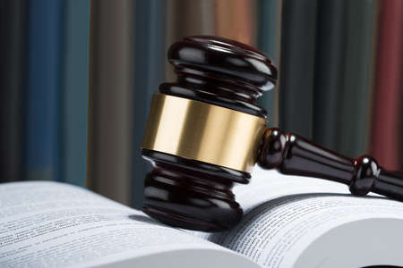 trial indoor: Close-up Of Wooden Gavel With Stack Of Book On Table Stock Photo