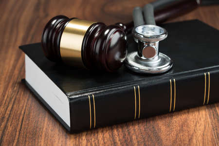 Close-up van de hamer en stethoscoop op Book Geplaatst Op Tafel