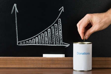 generous: Close-up Of A Person Inserting Coin In Donation Can In Front Of Blackboard Showing Graph Stock Photo