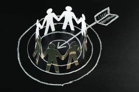 paper cutout: Circle Of White Paper Cut-out Figures Over Dart And Arrow Drawn On Blackboard With Chalk