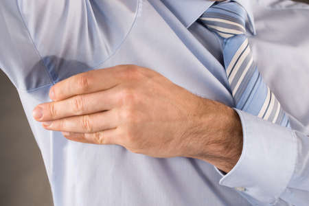 axila: Hombre Con Hiperhidrosis Sudoración Tocar Su Axila Foto de archivo