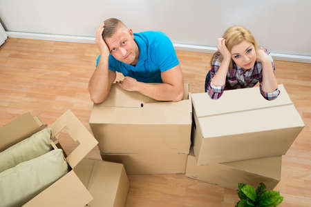 moving box: Portrait Of Worried Young Couple With Cardboard Boxes