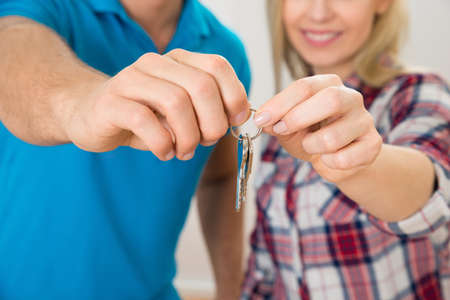 Close-up Of Couples Hand Holding Keys From new Home photo