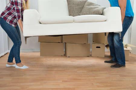 Gelukkig Jong Paar Dragende Couch In New Home Stockfoto