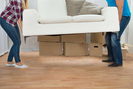 people moving: Happy Young Couple Carrying Couch In New Home Stock Photo