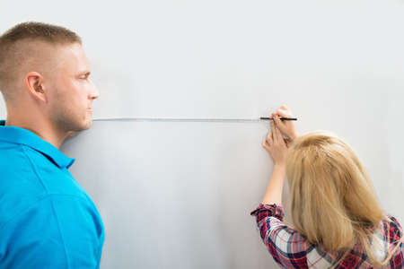 Close-up Of Young Couple Measuring Wall With Measurement Tape And Pencil photo