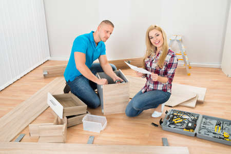assembling: Portrait Of Young Couple Assembling Furniture In New Home Stock Photo