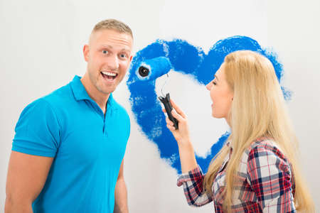 Portrait Of Young Couple Having Fun While Painting In New House photo