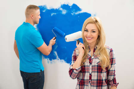 Portrait Of Young Woman Holding Paint Roller In Front Of Man Painting Wall photo