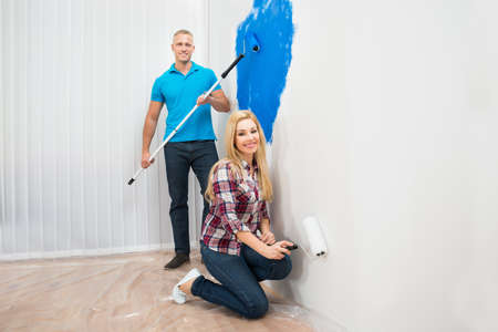 panting: Happy Young Couple Panting Wall Of Home Stock Photo