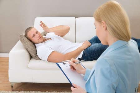 terapia psicologica: Mujer Psic�logo haciendo notas durante Psicol�gica Terapia Sesi�n