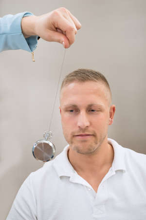 hypnosis: Close-up Of Psychiatrist Hypnotizing Young Man With Pendulum Stock Photo