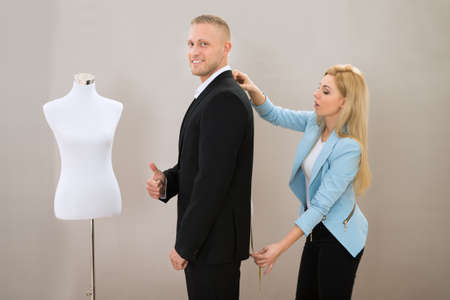 alterations: Female Tailor Taking Measurement Of Man Wearing Suit In Store