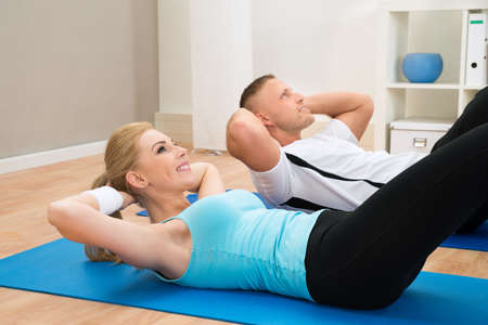 excercise: Portrait Of Young Couple Doing Crunches On Exercising Mat