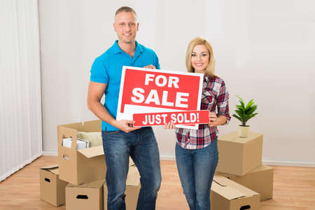 Happy Couple Holding Sold Sign In Their New Home