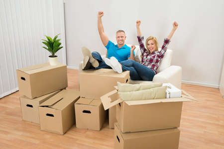 Excited Couple On Couch In Their New Home With Cardboard Boxes photo