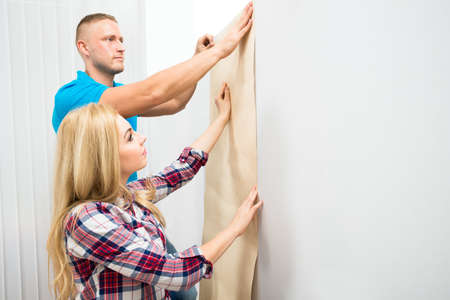 sticking: Portrait Of Young Couple Applying Wallpaper On Wall In New Home Stock Photo