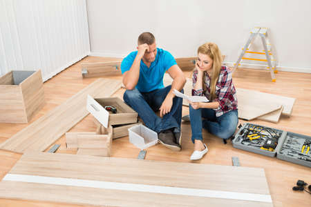 contemplated: Portrait Of Contemplated Couple With Disassembled Furniture Parts In New Home Stock Photo