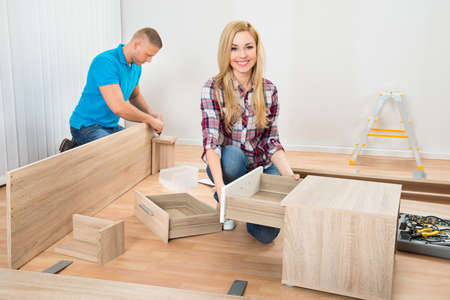 assembling: Portrait Of Young Couple Assembling Wooden Furniture In New Home Stock Photo