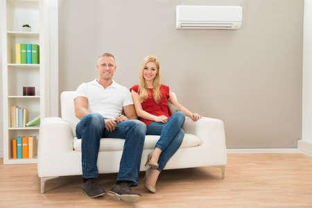 aire acondicionado: Joven pareja feliz sentado en el sofá blanco
