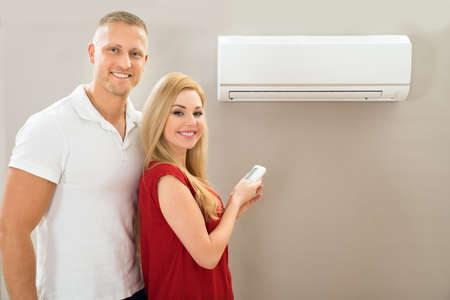 domestic: Portrait Of Happy Couple Holding Remote Control Air Conditioner Stock Photo